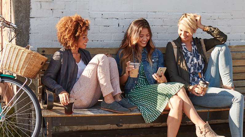 Three young women sitting on a bench using phones and having a conversation.